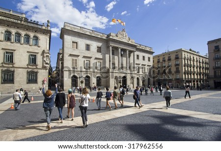 Barcelona, Spain - May 21, 2015: Tourists walk on the Placa de Sant Jaume in front of the City Halll of Barcelona, Spain on May 21, 2015. - stock photo