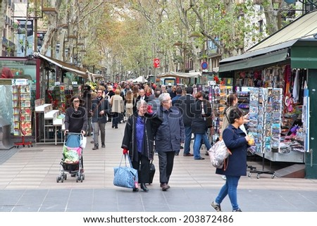 BARCELONA, SPAIN - NOVEMBER 6, 2012: People walk famous Rambla street in Barcelona, Spain. According to Mastercard, Barcelona is the 15th most visited city worldwide (7.5m in 2012). - stock photo