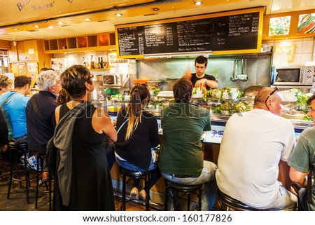 BARCELONA, SPAIN - OCTOBER 14: food stand in the market hall La Boqueria with unidentified people on October 14, 2013 in Barcelona. It is a famous and historical market hall on 2.600 square meters. - stock photo