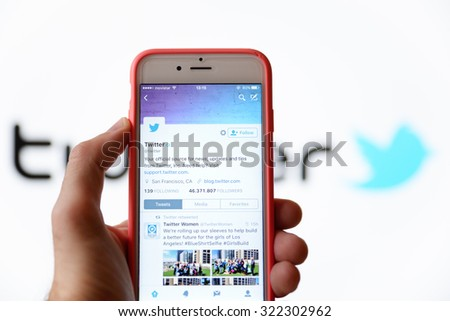 BARCELONA, SPAIN - SEP 30, 2015: Hand holding a mobile phone and using the social network Twitter application. - stock photo