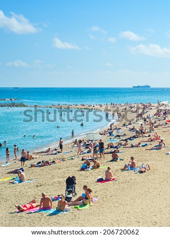 BARCELONA, SPAIN - SEPT 23, 2013: People at Barcelona city beach. 400 meters long, it is one of 10 best urban beaches of the world.  - stock photo