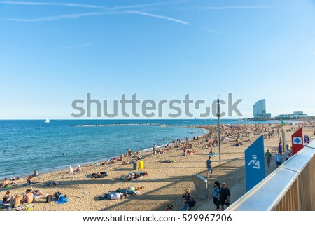 BARCELONA,SPAIN - SEPTEMBER 17; Barcelonetta Beach with architecturally modern W Hotel in distance, sunbathers along sandy beach September 17, 2016, Barcelona Spain