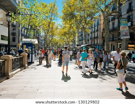 BARCELONA, SPAIN - SEPTEMBER 14: La Rambla on September 14, 2012 in Barcelona, Spain. Thousands of people walk daily by this popular pedestrian area 1.2 kilometer-long - stock photo