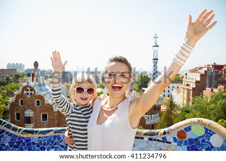Barcelona will show you how to remarkably spend holiday. Happy mother and baby at Park Guell rejoicing - stock photo