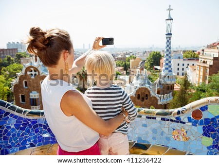 Barcelona will show you how to remarkably spend holiday. Mother and baby taking photos with digital camera at Park Guell - stock photo