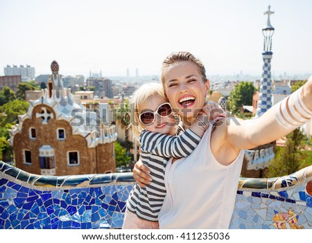 Barcelona will show you how to remarkably spend holiday. Smiling mother and baby taking selfie at Park Guell - stock photo