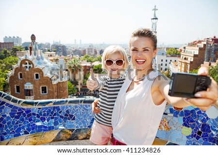 Barcelona will show you how to remarkably spend holiday. Smiling mother and baby taking selfie with digital camera at Park Guell - stock photo
