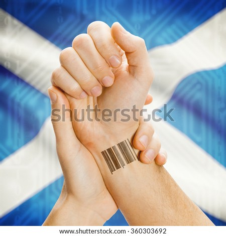Barcode ID number on wrist of a human and national flag on background series - Scotland
