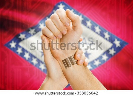 Barcode ID number tatoo on wrist and USA statesl flag on background - Arkansas