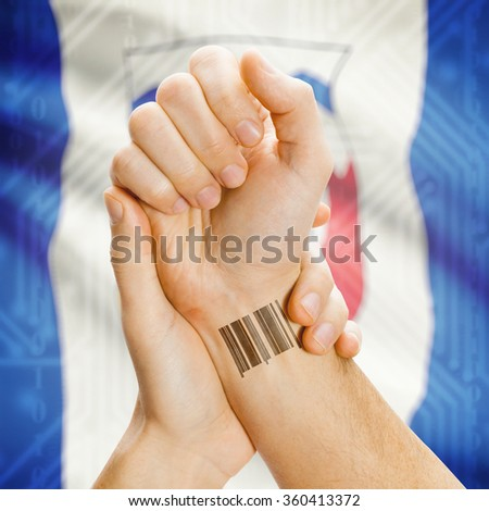 Barcode ID number tattoo on wrist and Canadian province flag on background - Northwest Territories