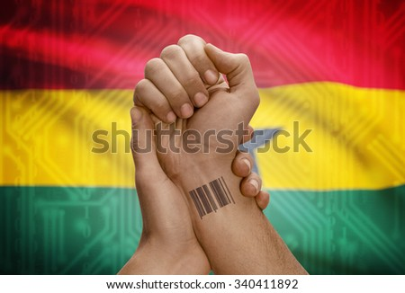 Barcode ID number tattoo on wrist of dark skinned person and national flag on background - Ghana - stock photo