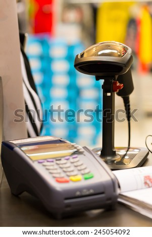 Barcode scanner on table with credit card machine (selective focus) - stock photo