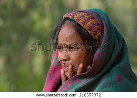 Bardia, Nepal - January 15, 2014: Portrait of old taru woman wearing traditional clothes in Bardia, Nepal
