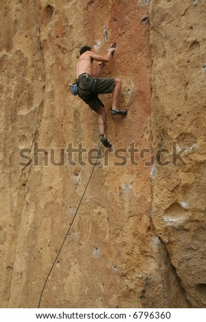 Bare back climber clinging to rock face,		Smith Rock State Park, 	Central Oregon - stock photo