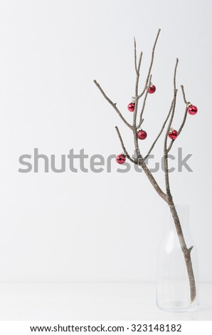 Bare branch with red christmas bauble minimalist, elegant style, plenty of copy space - stock photo