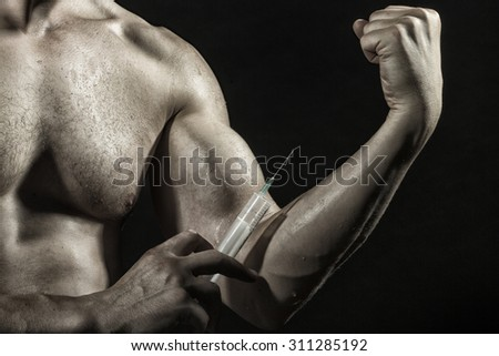 Bare chest and muscular male wet arm of young boy with big biceps and syringe with thin needl as symbol of medicine anabolocs or drugs making injection on black studio background, horizontal picture - stock photo
