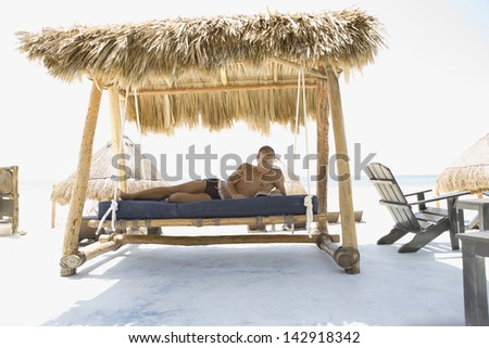 Bare chested man reading on a hammock at the beach - stock photo