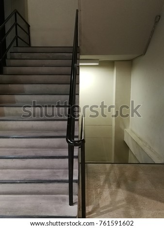 Bare Concrete Stairs Going Up And Down With Fluorescent Light And Black  Painted Handrail