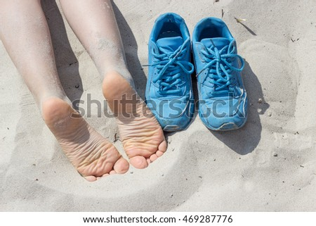 bare feet and blue shoes on the beach / beach holiday / at the beach