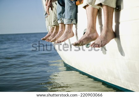 Bare feet hanging over side of boat - stock photo