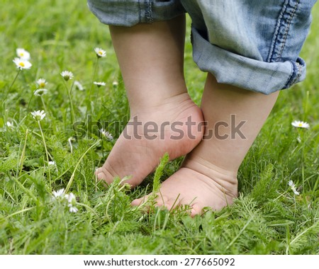 Bare feet of a small child in denim trousers on a grass lawn.  - stock photo