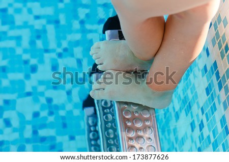 Bare feet of a young child underwater standing on the top rungs of a set of swimming pool steps, view from above looking into the cool blue water - stock photo