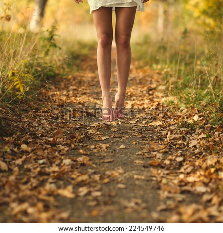 bare feet of a young girl on autumn road - stock photo