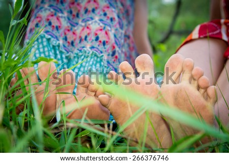 bare feet of girls which went on the ground on green grass - stock photo