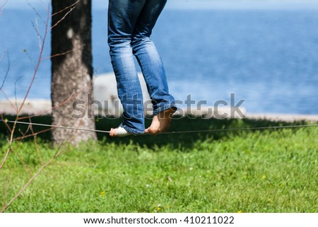 Bare feet on the rope, one of them with a bandage/Bare feet on the rope - stock photo