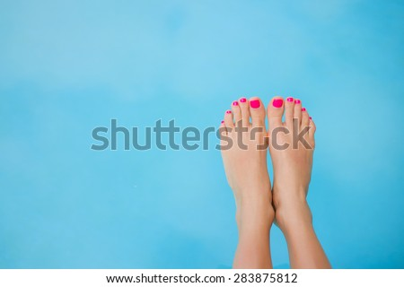 Bare feet over blue swimming pool water - stock photo