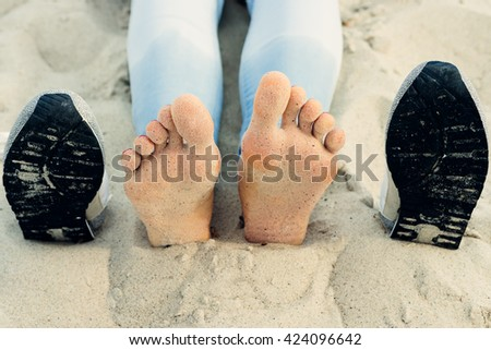 Bare female feet on the sand next to the shoes - stock photo