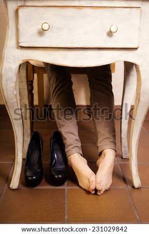 Bare female feet under the white vintage retro table. Tired ...