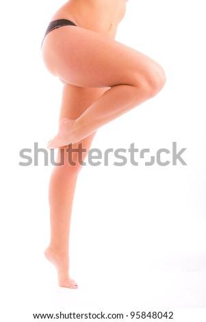 bare female legs bent in dancer's pose against white background - stock photo