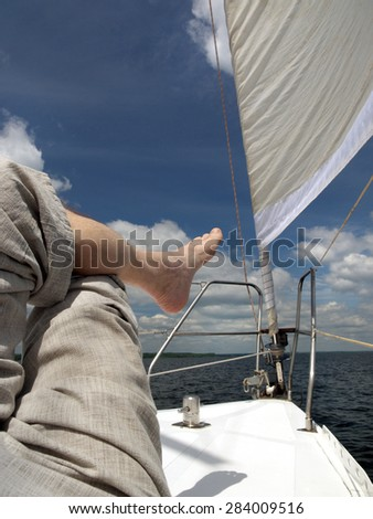 bare foot of a man who is lying on the deck of the yacht, blue sky, white clouds and sail - stock photo