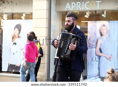 Bare Knuckle Parade band member play on accordion in Union street, Bath, England. 10.12.2015 - stock photo