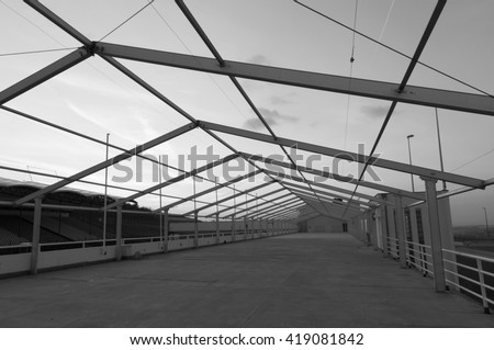 Bare metal frame of built factory storage hall building, black and white image