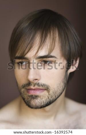 Bare-shouldered studio portrait of reflective young man