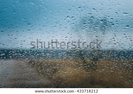 Bare trees and brown grass seen though glass with raindrops on overcast rainy autumn day. Focus on water drops.