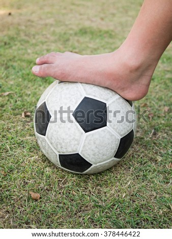 Bared foot of kid on the soccer ball