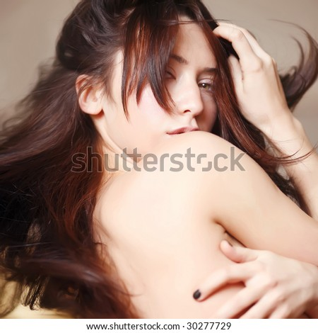 Bared shoulder of the girl with chestnut hair