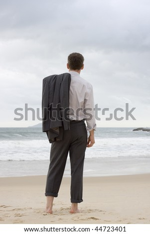 Barefoot businessman relaxing on a beach - stock photo