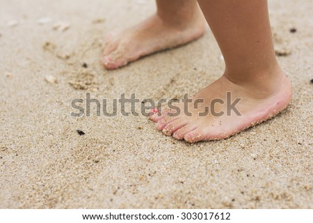 Barefoot child playing in the sand on the beach close to shallow water.