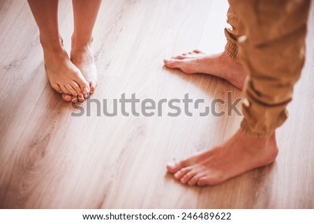 barefoot couple standing on wooden floor no face  - stock photo
