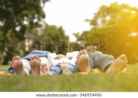 barefoot family lie on their backs in the green grass in a sunny spring park. - stock photo