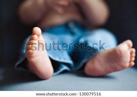 barefoot feet baby 7 months in jeans on a chair