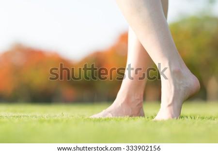 Barefoot feet walking on grass - stock photo