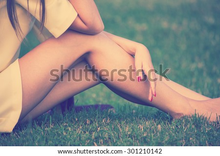 barefoot female legs in grass retro colors - stock photo