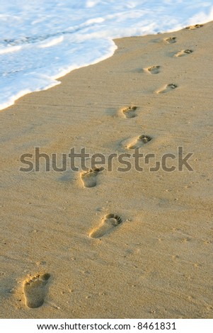 Barefoot footprints on the beach leading in the water