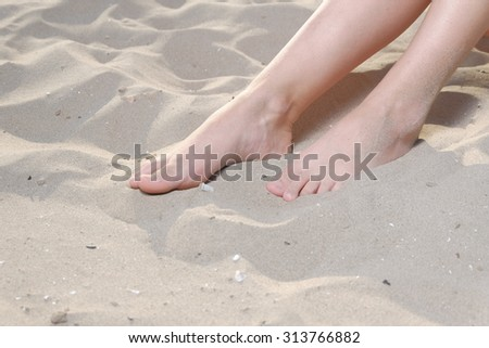 Barefoot girl sitting on sand a lot of space for text. Woman sandy feet without nail polish on sandy beach. - stock photo