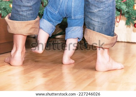 Barefoot legs of father and baby boy near christmas tree. Man and (child) kid are walking. Caucasian male model. New year concept. Close up, indoors.  - stock photo